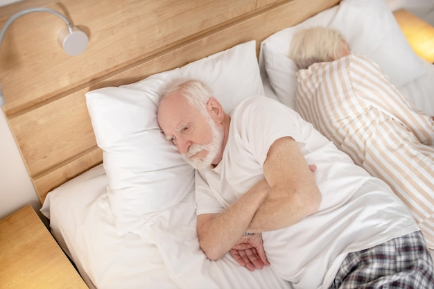Sleeplessness. aged married couple lying in bed back to back trying to fall asleep