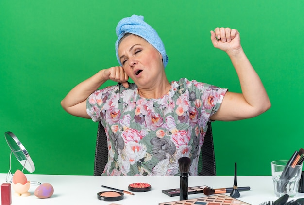 Sleepy adult caucasian woman with wrapped hair in towel sitting at table with makeup tools yawning