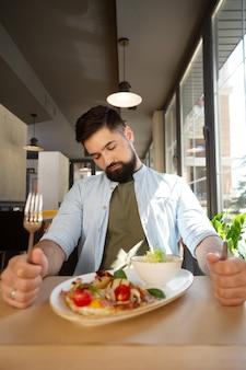 졸리고 배고프다. 식당에서 먹고 싶어하는 동안 칼과 포크를 들고 졸린 수염 난 남자