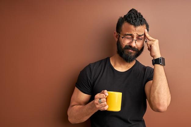 茶色の背景で隔離の朝のコーヒーと眠そうなアラビア語の男
