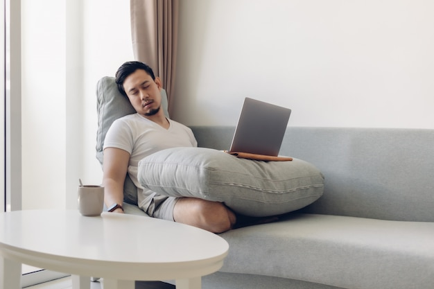 Sleepy asian man working on his laptop on the sofa.