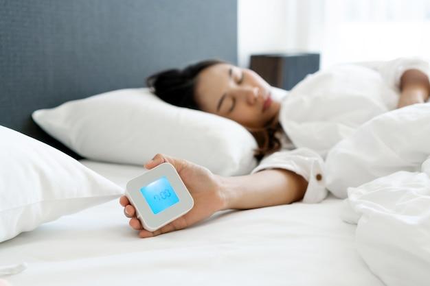 Сонная азиатская женщина, лежа в постели, выключает будильник по утрам