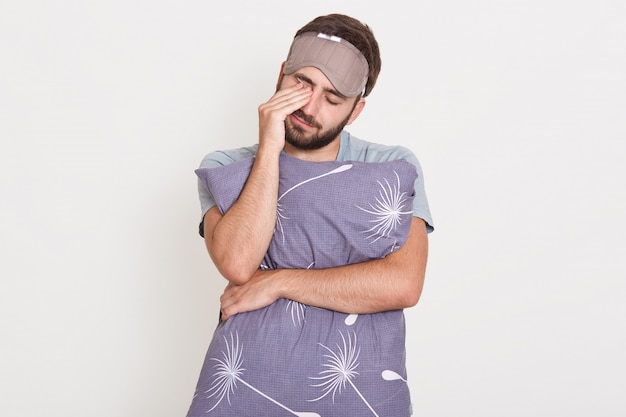 Sleepy bearded male posing with closed eyes isolated over white wall, rubbing his eyes with hand, embracing pillow