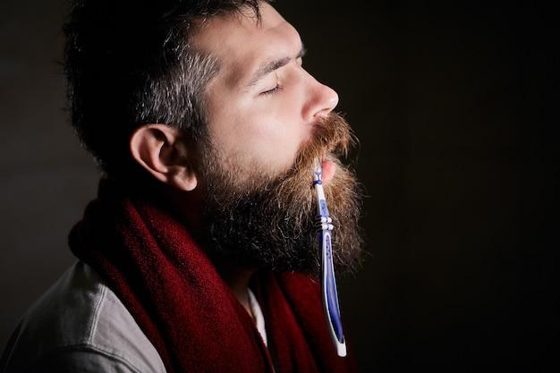 아침에 화장실 거울 앞에서 칫솔로 양치질하는 졸린 수염 난 남자.