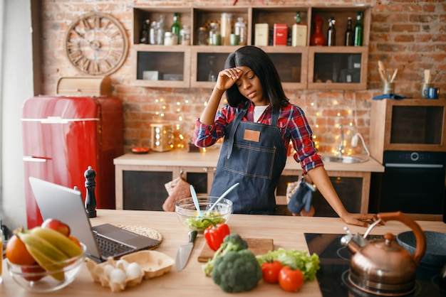 Сонная черная женщина в фартуке готовит здоровый завтрак на кухне. африканская женщина готовит овощной салат дома