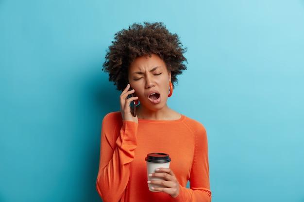 졸린 지루한 아프리카 계 미국인 여성은 스마트 폰 음료를 통해 이야기하는 동안 흥미롭지 않은 이야기를 듣는다 테이크 아웃 커피는 파란색 벽 위에 고립 된 귀걸이가 달린 주황색 점퍼를 착용합니다.
