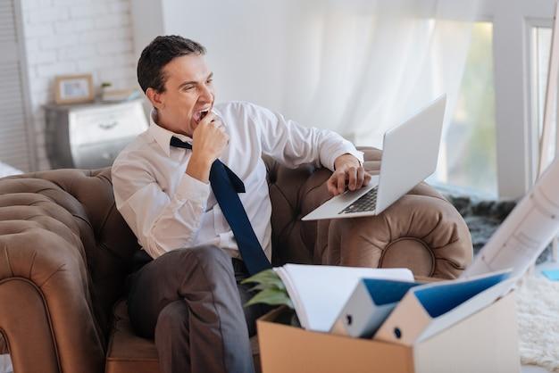 졸리는. 자신의 현대 노트북 화면을 보면서 하품을하고 개인 물품 상자가 옆에 서있는 동안 피곤한 지루한 우아한 남자
