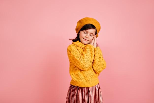 분홍색 벽에 서 졸린 갈색 머리 아이. 눈을 감고 포즈를 취하는 아이.
