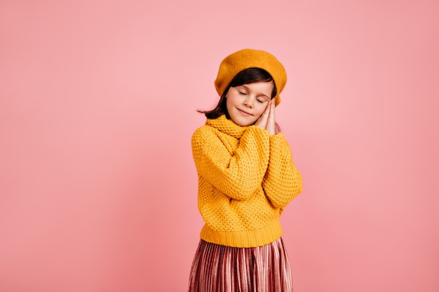 Sleepy brown-haired child standing on pink wall.  kid posing with eyes closed.