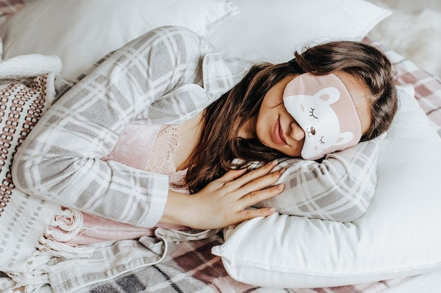 A sleepy brunette girl lies in bed with a blindfold in cute pajamas