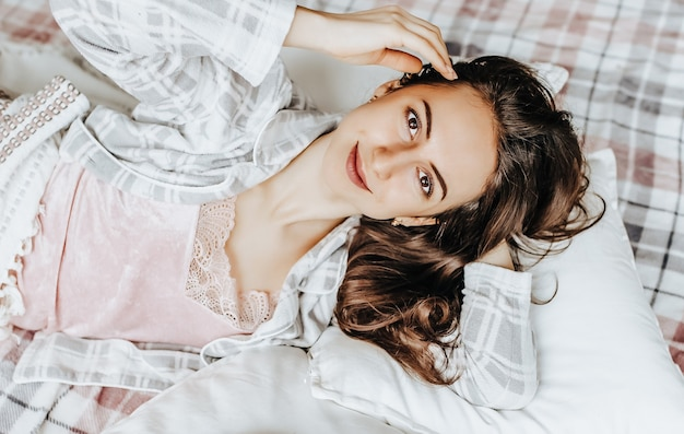 A sleepy brunette girl lies in bed with a blindfold waking up in the morning