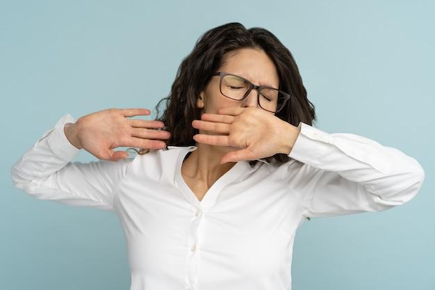 眠そうなビジネスウーマンは退屈な眼鏡をかけ、目を閉じてあくびをし、手で口を覆います。疲れ果てたサラリーマン、睡眠不足、不眠症、スタジオでの隔離