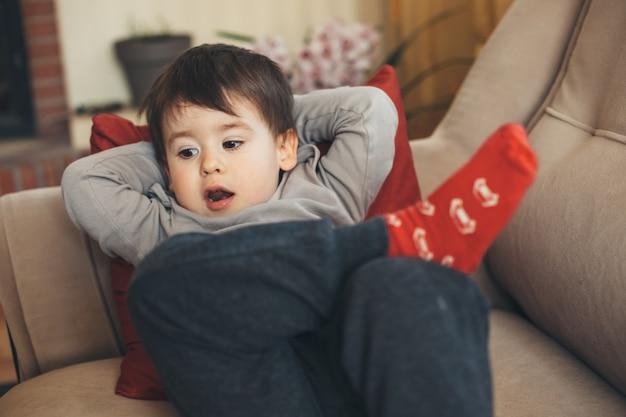 昼寝の準備ができて横たわっているソファでポーズをとって赤い靴下を持つ眠そうな白人の少年