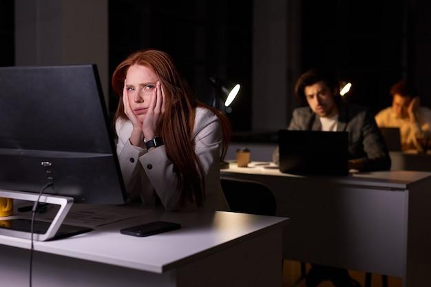 밤에 사무실 책상에 앉아 옆을 바라보는 졸린 백인 여성, 여자는 집에 가고 싶어하고, 손에 기대고, 공식적인 옷을 입고 있습니다. 작업, 비즈니스, 마감 개념