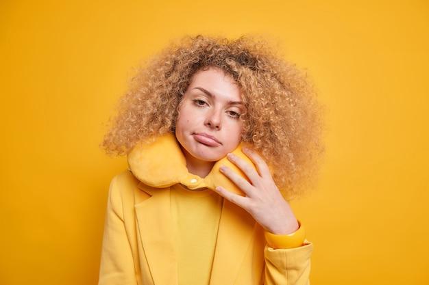 Сонная кудрявая женщина с усталым выражением лица чувствует себя измученной после долгой поездки, носит надутую подушку на шее для комфорта, наклоняет голову, одетая формально изолированно над желтой стеной