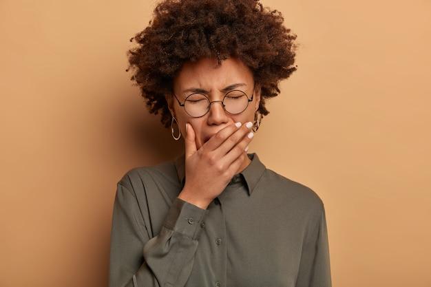 졸린 곱슬 곱슬 한 여자가 눈을 감고 하품하고 입을 가리고 피곤하며 수면과 에너지가 부족하며 휴식이 필요하며 불면증으로 고통받습니다.