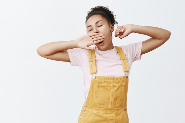 Сонная милая темнокожая женщина в модном желтом комбинезоне, растягивается и зевает, прикрывая открытый рот ладонью и закрытыми глазами, желая спать, рано просыпаясь