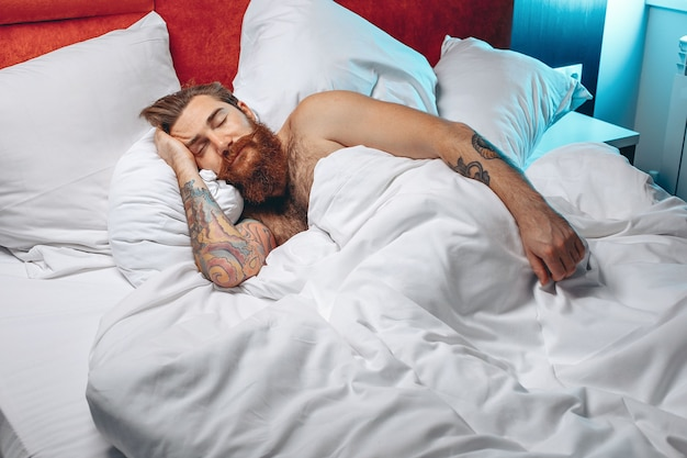 Sleepy cute and tired man with a long mustache and beard lying on a white bed under the covers and sleeping.