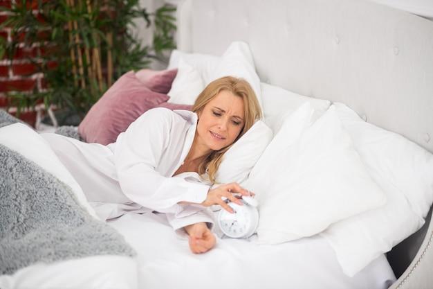 Сонная недовольная взрослая женщина в белой рубашке в постели выключает будильник