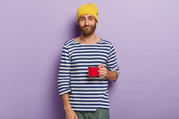 Sleepy dissatisfied man has morning routine, being tired after sleepless night, wears yellow hat and striped jumper