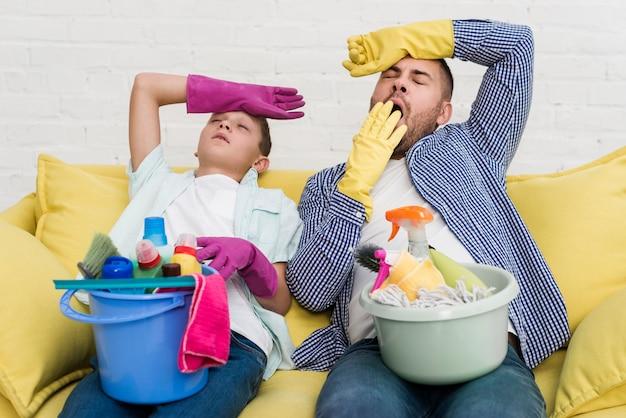 家を掃除した後、ソファーで休んでいる眠そうな父と息子
