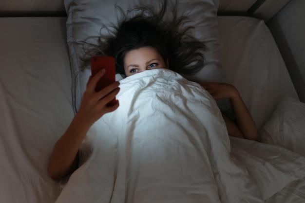 夜、ベッドでスマートフォンを見ている眠そうな女性。ガジェットへの依存。
