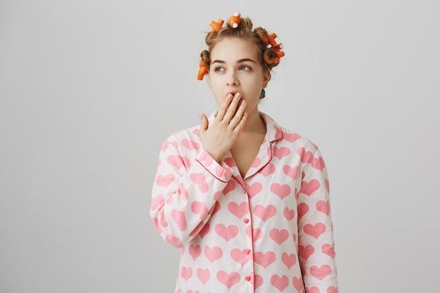 Ragazza sonnolenta in bigodini e pigiama svegliarsi la mattina, sbadigliando