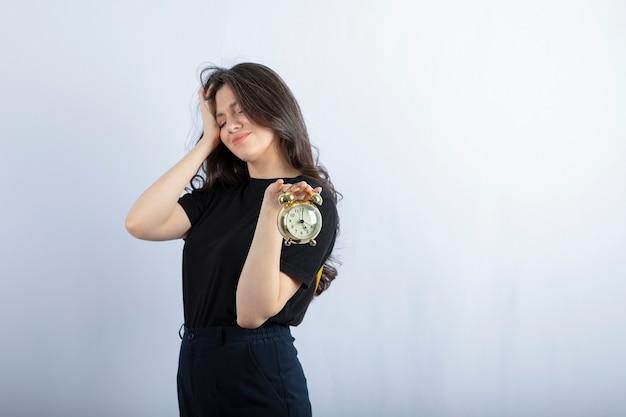 Сонная девушка держит будильник на белой стене.