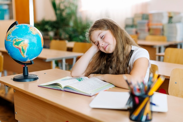 Ragazza sonnolenta sulla lezione