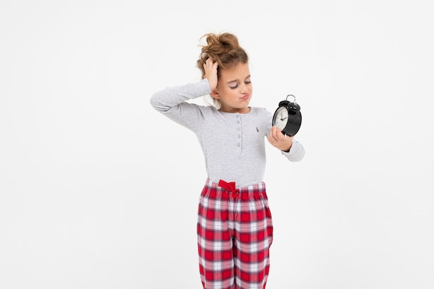 Sleepy girl in pajamas just woke up and yawns while holding an alarm clock on a white with copy space