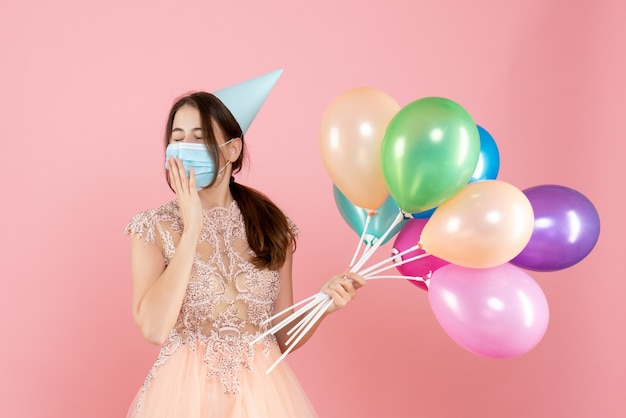 Sleepy girl with party cap and medical mask holding colorful balloons on pink