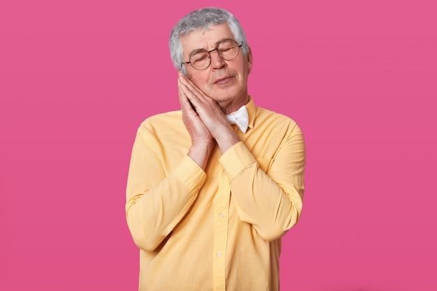 Сонный седой зрелый мужчина в желтой рубашке с бабочкой позирует руками вместе, стоя с закрытыми глазами на розовой стене. мужчина с короткой прической хочет пойти плохо. концепция людей.