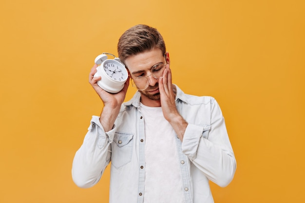 Sleepy guy with brown hair in eyeglasses, trendy jacket and light t-shirt posing with alarm clock on isolated wall
