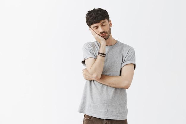 Sleepy handsome guy posing against the white wall