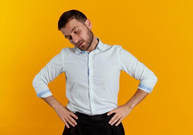 졸린 잘 생긴 남자는 오렌지 벽에 고립 된 허리에 손을 넣습니다