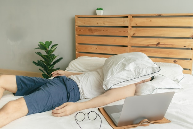 Сонный ленивый человек работает из дома, но спит перед ноутбуком.