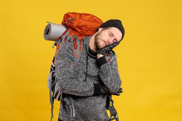 革手袋とバックパックを持つ眠い男性のヒッチハイカー