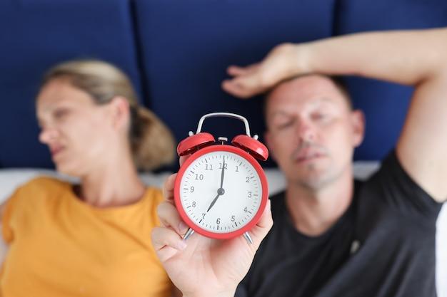 졸린 남자와 여자는 침대에 누워 빨간색 알람 시계 근접 촬영을 들고