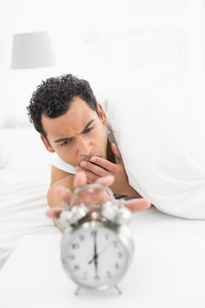 Sleepy man in bed extending hand to alarm clock
