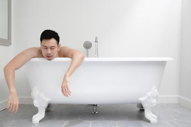 疲れてリラックスの概念で白い浴槽で眠そうな男