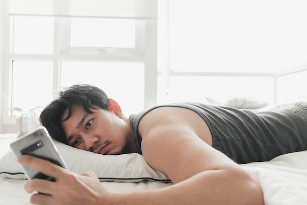 Сонный человек использует смартфон лежа на кровати.