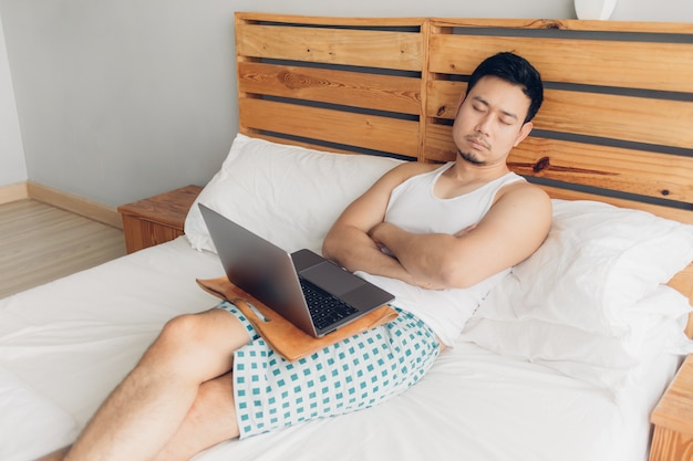 Sleepy man is working with his laptop on his cozy bed. concept of boring freelancer lifestyle.