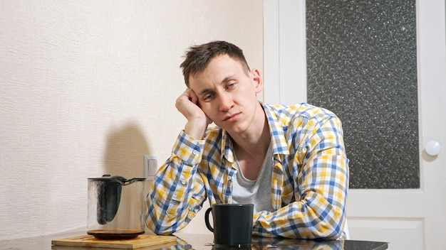 Sleepy man pours coffee while sitting at the table in the kitchen