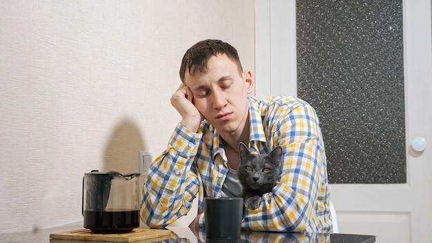 Сонный мужчина сидит с серым котом за столом на кухне