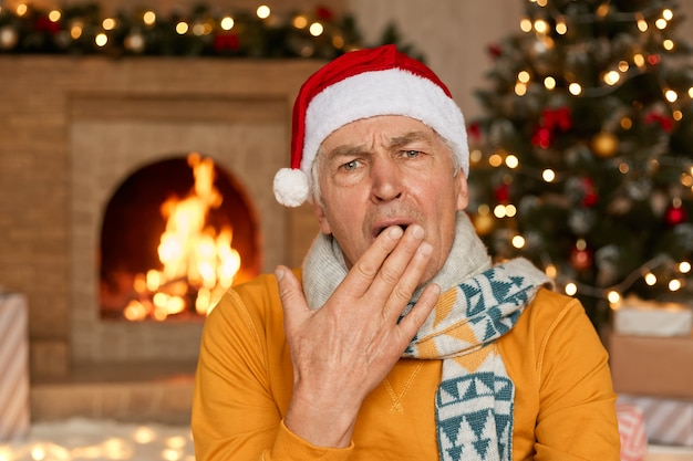 Sleepy man in yellow sweater, scarf and christmas hat yawning, covering mouth with hand on background of fireplace and fir tree, happy new year, celebration holiday at home.