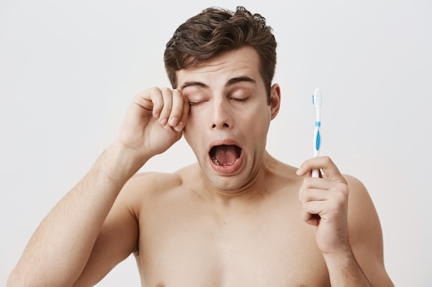Sleepy muscular guy with dark hair, woke up early in the morning, getting ready for work or university, yawning, opening widely his mouth, holding toothbrush in his hand, and rubbing his eye.