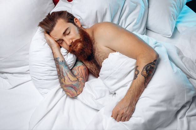 Sleepy pretty and adult man with a long mustache and beard lying on a white bed under the covers and sleeping.