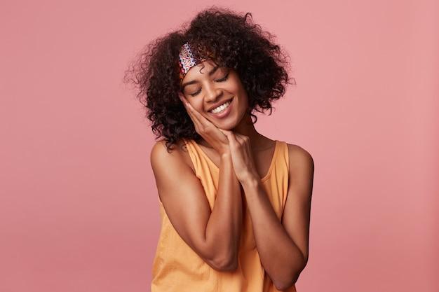 Femmina bruna riccia dalla pelle scura sonnolenta con taglio di capelli corto che appoggia la guancia sulle mani alzate e tiene gli occhi chiusi, sorridendo sinceramente mentre posa