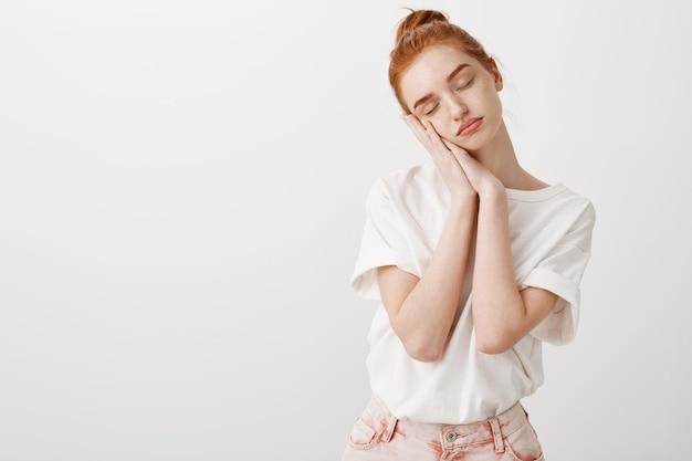Сонная рыжая девушка, опираясь на ладонь с закрытыми глазами, вздремнув
