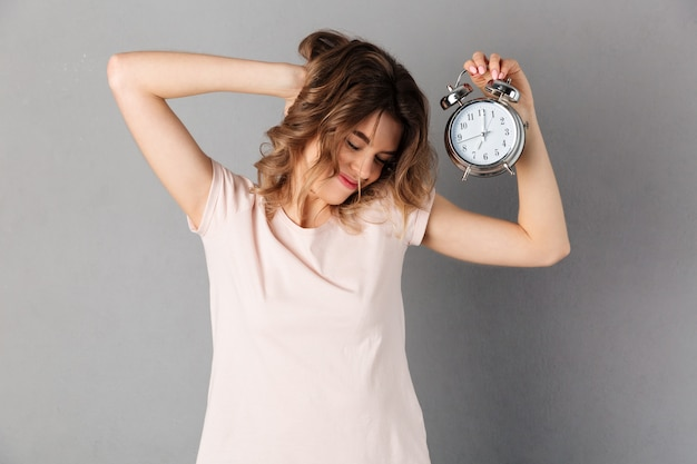 Sleepy smiling woman in t-shirt wake up while holding alarm clock with closed eyes over grey